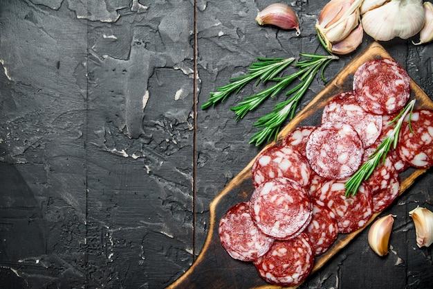 Gesneden salami met aromatische kruiden en kruiden. op zwarte rustieke achtergrond.