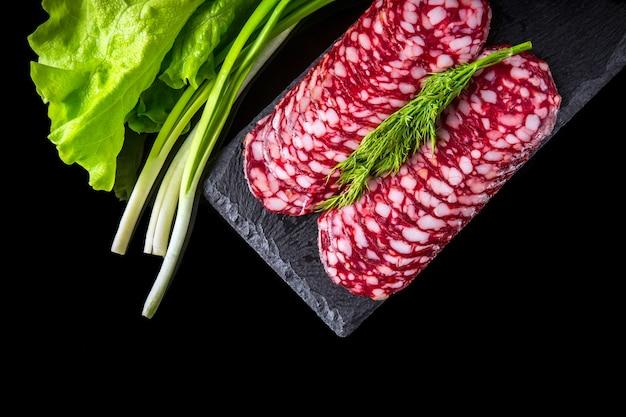Gesneden salami met dille en groene salade op een lei bord serveren zwarte geïsoleerde achtergrond