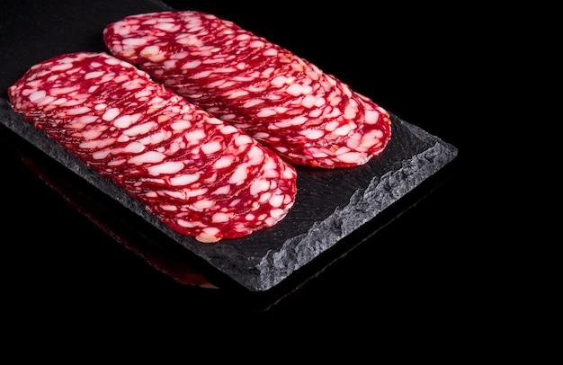 Gesneden salami op een lei bord serveren zwarte geïsoleerde achtergrond