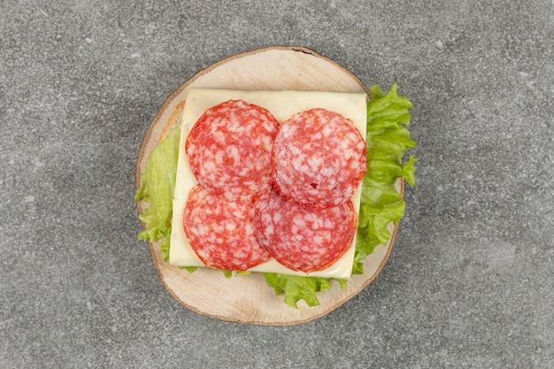 Gesneden salami op houten stuk met kaas en sla