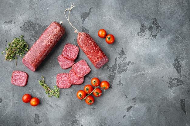 Gesneden salami set, op grijze stenen tafel, bovenaanzicht plat gelegd