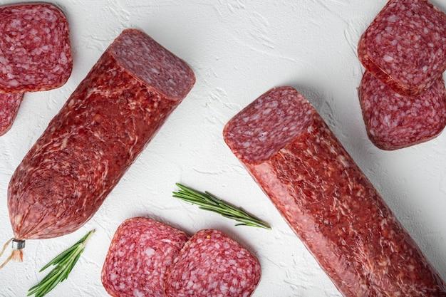 Gesneden salami set, op witte stenen tafel