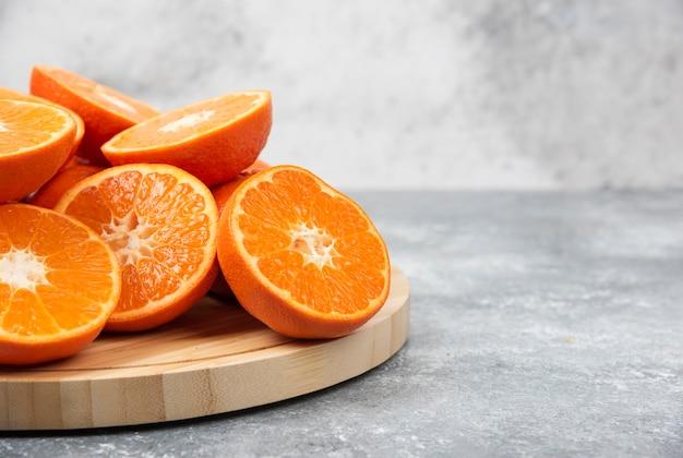 Gesneden sappig vers oranje fruit in een houten plaat.
