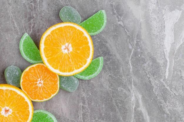 Gesneden sappige sinaasappel en groene marmeladesuikergoed op marmeren oppervlak.