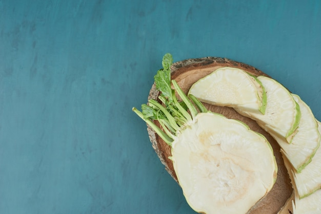 Gesneden selderij maïs op blauw op een houten bord.