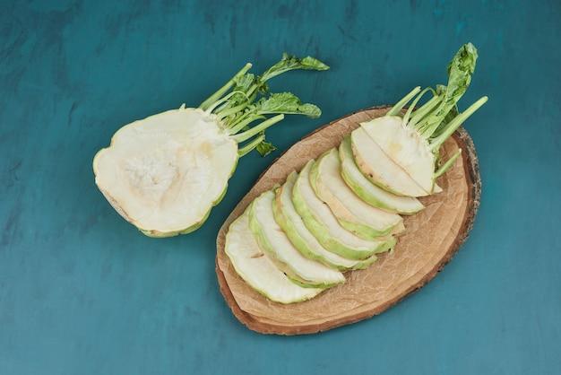 Gesneden selderij maïs op een houten bord.