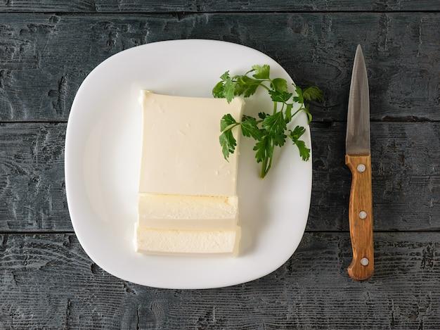 Gesneden servische kaas met een mes en peterselie op de dorpstafel.
