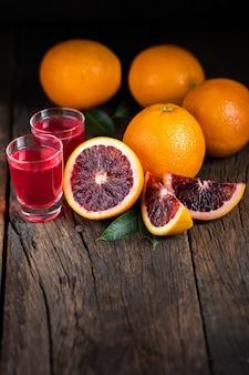 Gesneden siciliaanse bloedsinaasappelenvruchten over oude donkere houten achtergrond.
