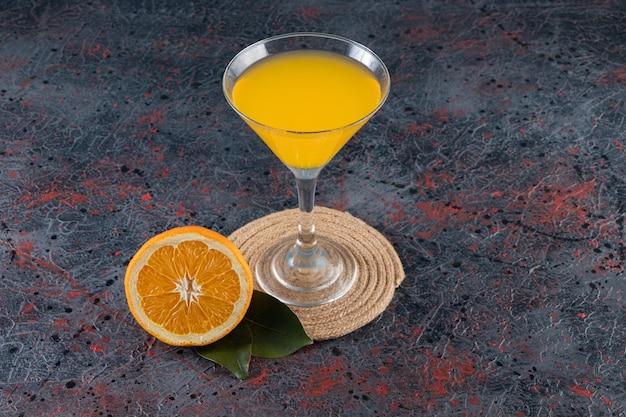 Gesneden sinaasappel en glas sap op een onderzetter, op de gemengde tafel.