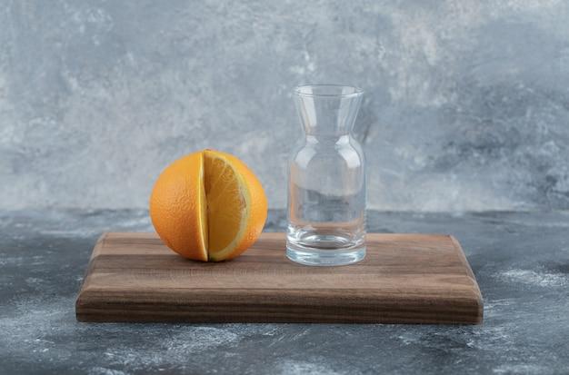Gesneden sinaasappel en leeg glas op een houten bord.