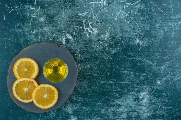 Gesneden sinaasappel naast perensap op het bord, op de blauwe tafel.