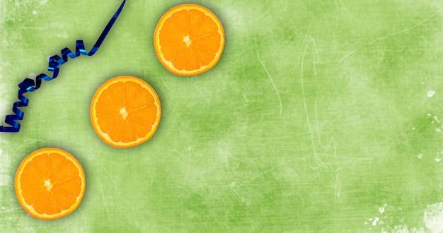 Gesneden sinaasappel op een groene achtergrond flatlay