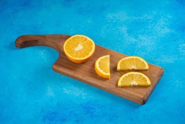 Gesneden sinaasappel op een houten bord op blauw.