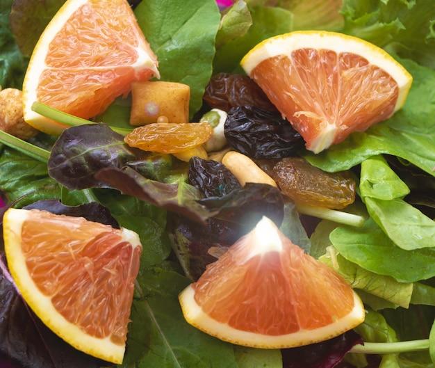 Gesneden sinaasappel op groene groente met bonen en rozijnen, salade gemengd, lensflare-effect
