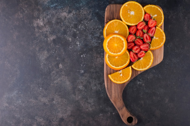 Gesneden sinaasappelen en aardbeien op een houten bord, bovenaanzicht