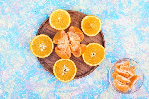 Gesneden sinaasappelen en mandarijnen die op een houten schotel worden geïsoleerd. hoge kwaliteit foto