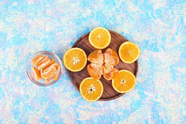Gesneden sinaasappelen en mandarijnen geïsoleerd op een houten schotel en in een glazen beker