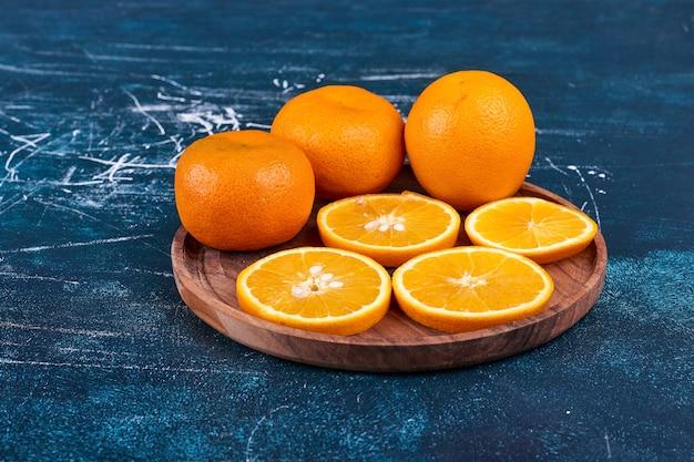 Gesneden sinaasappelen en mandarijnen op een houten schotel