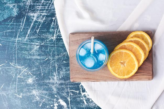 Gesneden sinaasappelen met een glas sap op blauw.