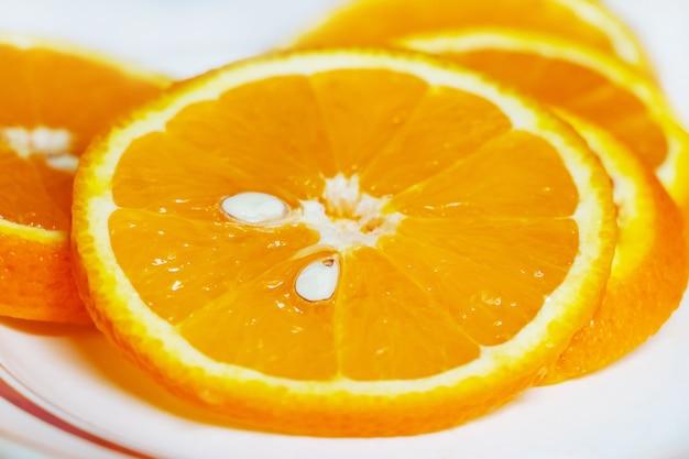Gesneden sinaasappelschijfjes op een bord, citrusvruchten