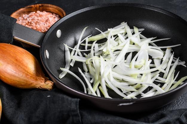Gesneden sjalot in een pan, gebakken uien koken. zwarte achtergrond. bovenaanzicht