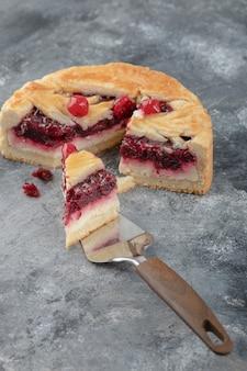 Gesneden smakelijke cheesecake met bessen op marmeren oppervlak.