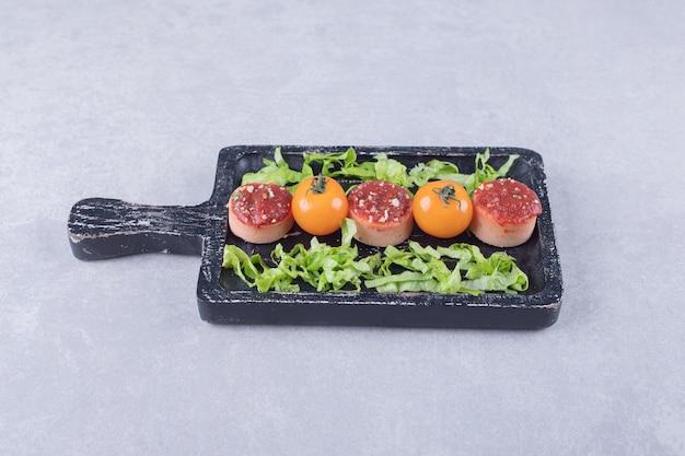 Gesneden smakelijke worstjes met ketchup en tomaten op zwart bord.