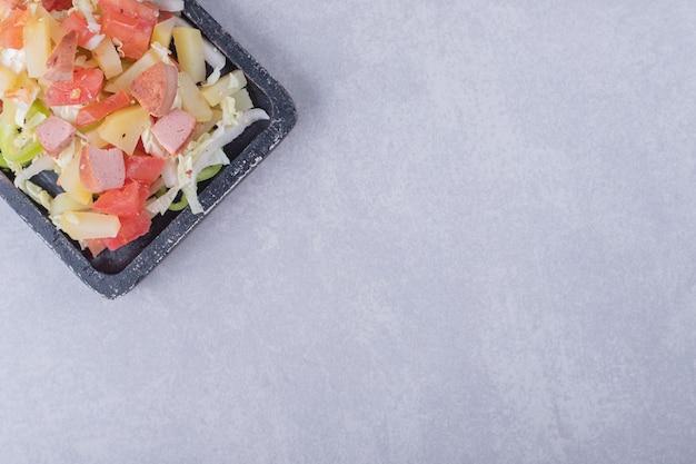 Gesneden smakelijke worstjes met verse salade op zwart bord.