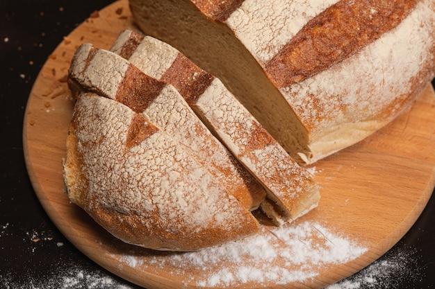 Gesneden sneetjes vers brood op een houten bord.