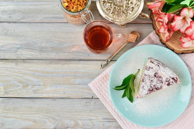 Gesneden stuk cottage cheese cake met frambozen op een achtergrond van suikerpot en thee uitzicht vanaf de top. zomer ontbijt.