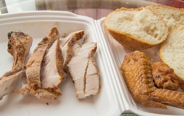 Gesneden stukjes koud gebakken varkensvlees in een plastic container, met sneetjes tarwebrood en gebakken kippenvleugel, een smakelijke snack.
