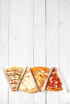 Gesneden stukjes pizza op een houten achtergrond, bovenaanzicht, plaats voor tekst