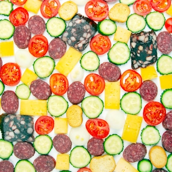 Gesneden stukjes worst, salami, kaas, komkommer en tomaat op een witte achtergrond. fast food. ingrediënten voor pizza. calorieën en dieet