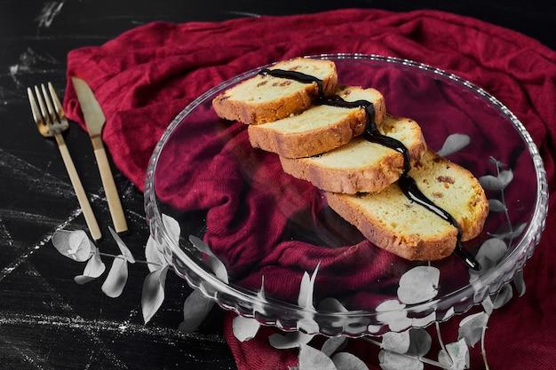 Gesneden taart in een glazen schotel met chocoladesiroop.