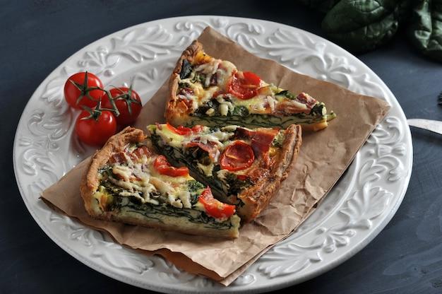 Gesneden taart met eieren, verse spinazie, tomaten, spek en kaas