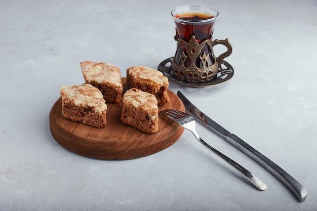 Gesneden taart op een houten schotel met een glas thee op een witte ondergrond.