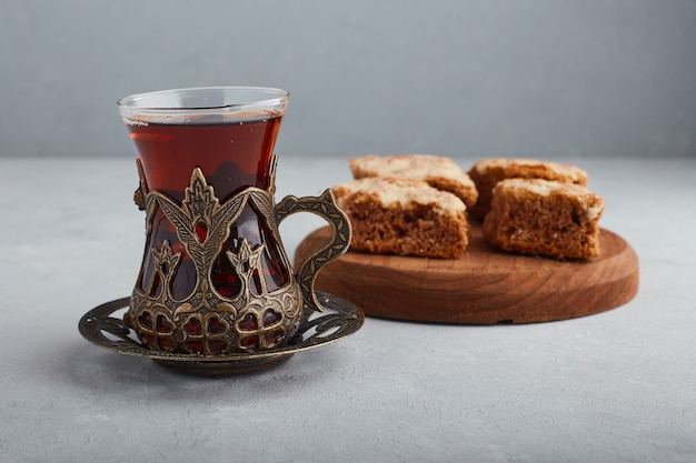 Gesneden taart op een houten schotel met een glas thee.