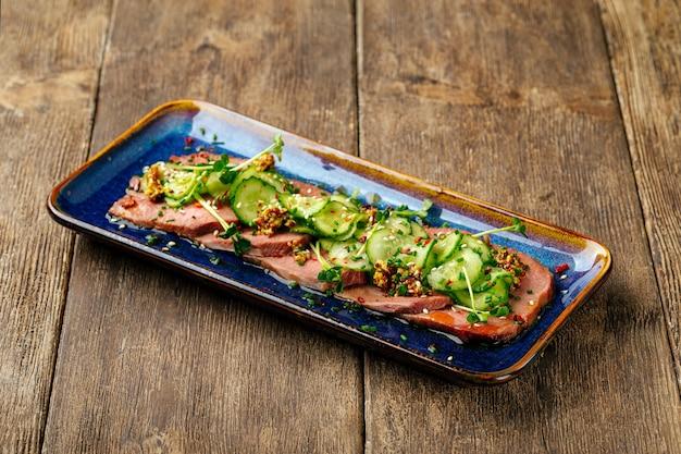 Gesneden tataki rosbief tong met zeewier chuka op het houten oppervlak