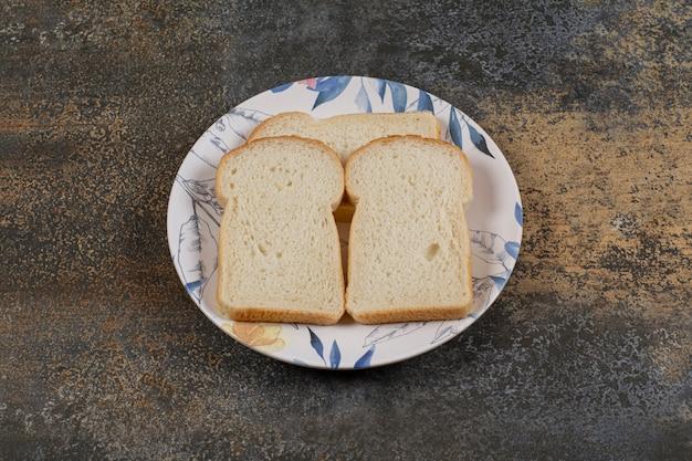 Gesneden toastbrood op kleurrijke plaat