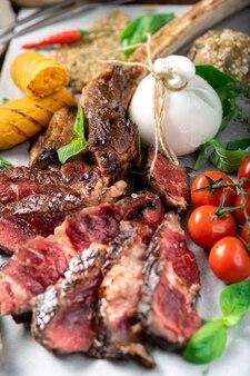Gesneden tomahawk steak gegrild in italiaanse stijl met burata kaas, basilicum en tomaten op een houten bord