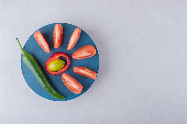Gesneden tomaten en chili peper op een bord op marmeren tafel.