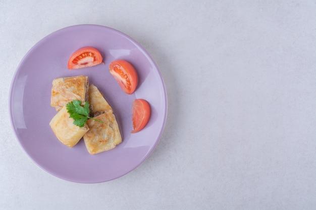 Gesneden tomaten en pannenkoek met vlees op plaat op marmeren tafel.
