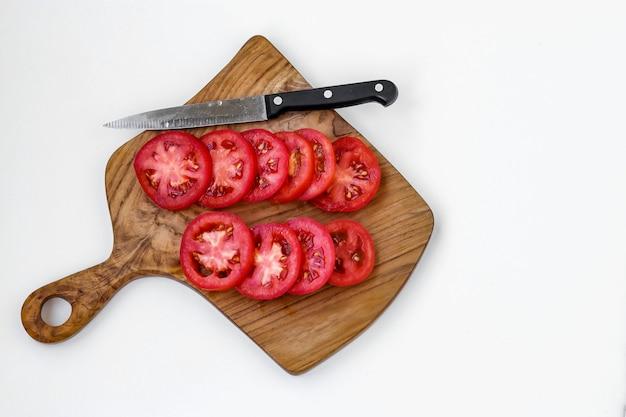 Gesneden tomaten geïsoleerd op een houten bord op een witte achtergrond, bovenaanzicht, kopieer ruimte