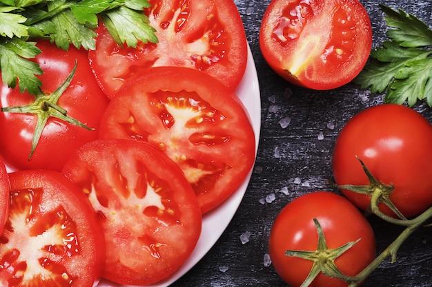 Gesneden tomaten op een witte plaat met zout