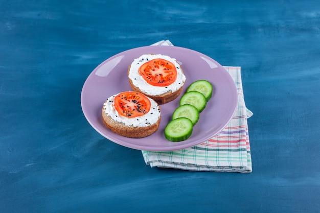 Gesneden tomaten op kaasbrood naast komkommer op een plaat op theedoek, op blauw.