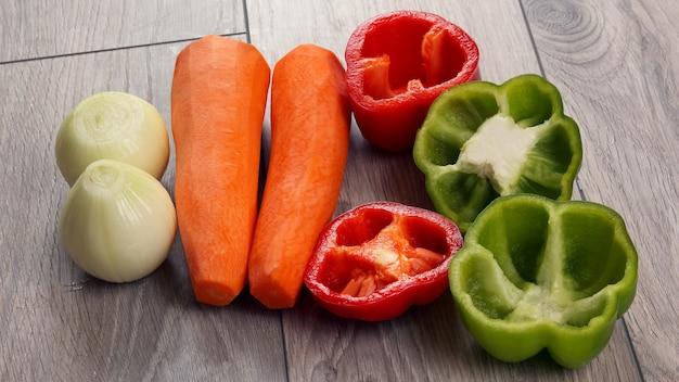 Gesneden ui en peper op een keukenbord met en wortelen. gezond en vitamine eten