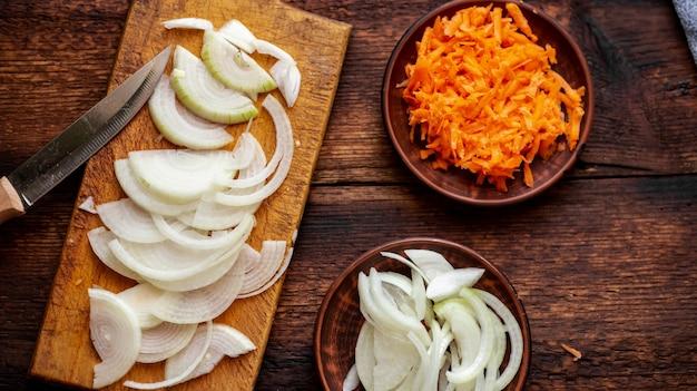 Gesneden uien en wortelen op een donkere houten achtergrond. ingrediënten, voorbereiding voor het koken.