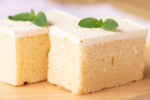 Gesneden van cheesecake met muntblaadjes versierd op de top.