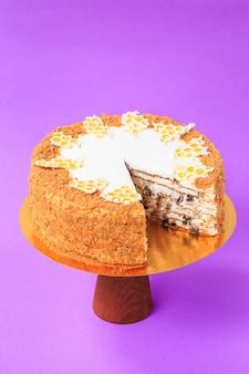 Gesneden verjaardagstaart op de houten taartstandaard. mooie biscuit op de achtergrond van papier. ruimte kopiëren. voedselfotografie voor recept.