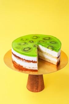Gesneden verjaardagstaart versierd met groene gelei en kiwi bovenop op de houten taartstandaard. mooie biscuittaart met slagroom. gele achtergrond. ruimte kopiëren. voedselfotografie voor recept.